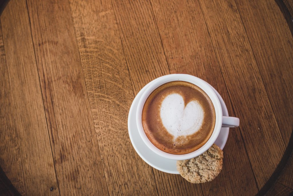 Coffee with heart in foam and biscuit